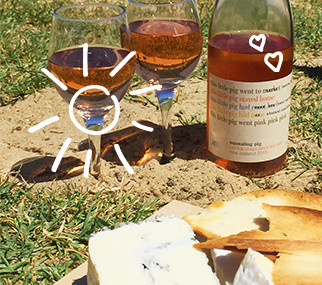 Bottle and glasses of Squealing Pig wine on ground next to a cheese platter